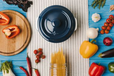 top view of pan and uncooked pasta with vegetables on blue table