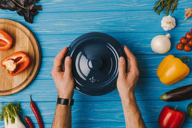 cropped image of man putting pan on blue table