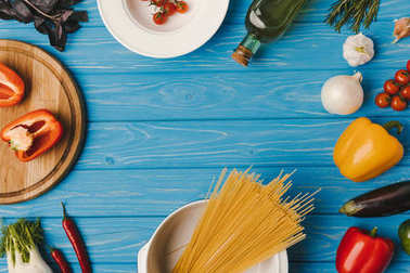 top view of uncooked pasta and vegetables on blue table