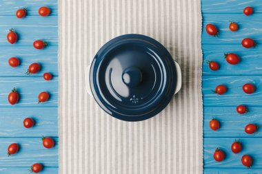 top view of cherry tomatoes with pan on blue table