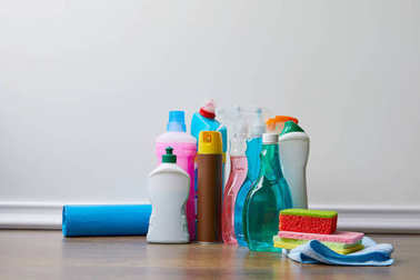 different bottles with domestic supplies for spring cleaning on wooden floor