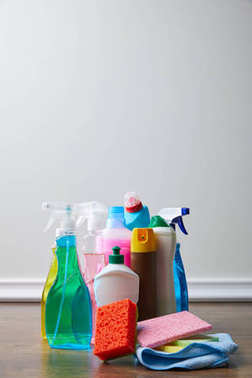 bottles with cleaners and spray bottles on floor for spring cleaning
