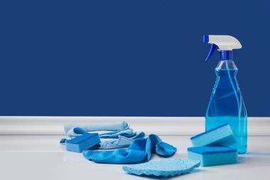 blue spray, rags and washing sponges for spring cleaning on white floor