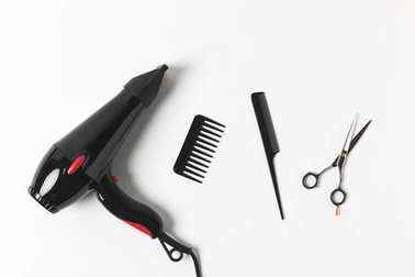 top view of hair dryer, combs and scissors, on white