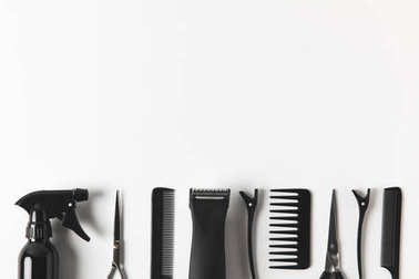 top view of hair clipper and hairdressing tools in row, on white
