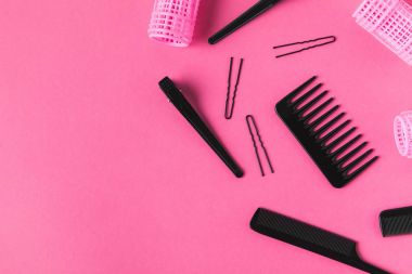 Flat lay with curlers and hairdressing tools, on pink stock vector