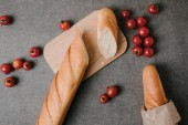 pohled shora bagety, Dřevěná deska a čerstvá rajčata na grey
