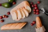pohled shora nakrájená bageta na dřevěné desce, čerstvých rajčat a avokáda na grey