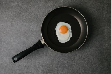 top view of frying pan with tasty fried egg on grey