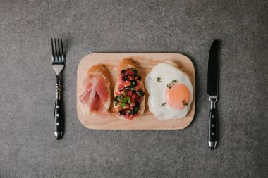 top view of gourmet antipasto bruschetta with fried egg and fork with knife on grey