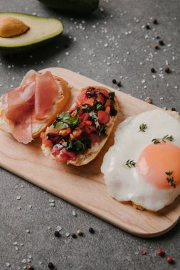 close-up view of delicious antipasto bruschetta and fried egg on wooden cutting board