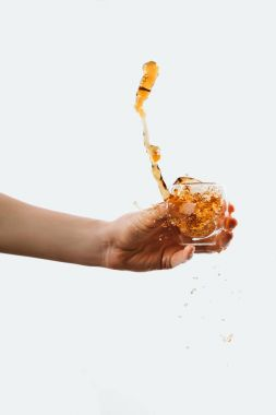 cropped view of hand holding glass with splashing coffee, isolated on white