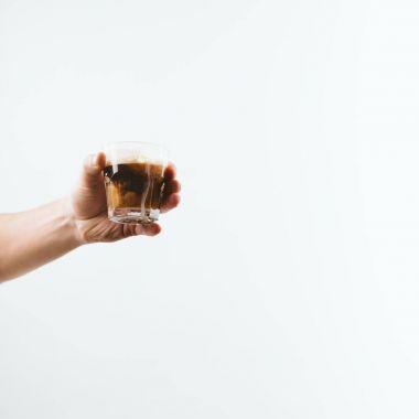 cropped view of hand holding glass full of coffee with milk, isolated on white