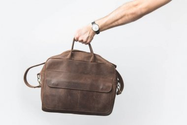 partial view of man holding leather bag in hand isolated on white