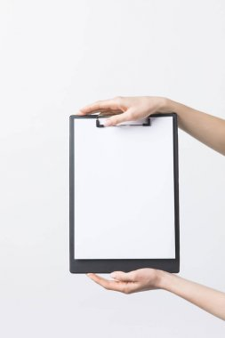 partial view of woman holding blank clipboard in hands isolated on white
