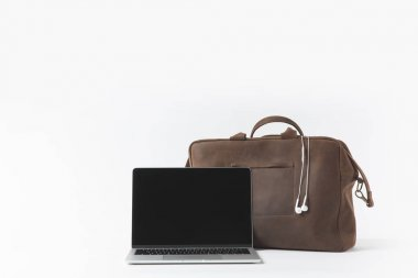 close up view of laptop with blank screen and stylish bag with earphones isolated on white