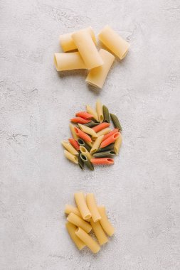 top view of piles of different raw pasta in row on concrete surface