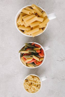 top view of various types of raw pasta in bowls standing in row on concrete tabletop