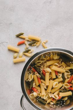 top view of various types of raw pasta in colander on concrete tabletop