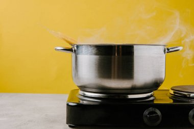 close-up shot of spaghetti boiling in stewpot on yellow