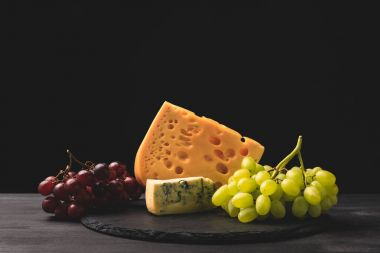 Blue cheese and emmental on board with grapes on black
