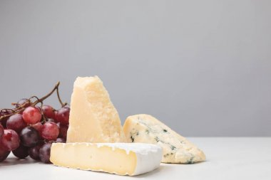 Closeup view of three types of cheese and grapes on gray