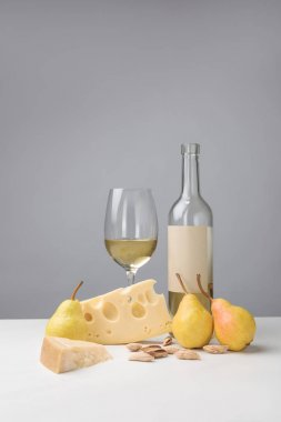 Cheddar and maasdam cheese, pears, almond, wine glass and bottle on gray
