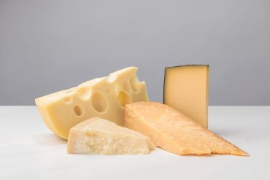 Closeup view of different types of cheese on gray