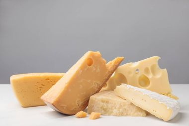 Close up shot of different types of cheese on gray