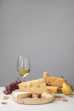 Different types of cheese on wooden boards, wine glass, fruits and almond on gray
