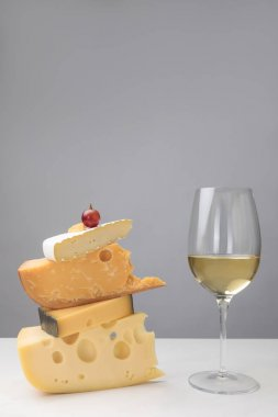 Close up view of white wine glass and grape on stack of different types of cheese on gray stock vector