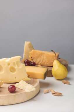 Closeup shot of different types of cheese on wooden boards with grapes and pear on gray