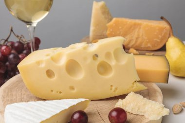 Closeup shot of different types of cheese on wooden board, pear, grapes and wine glass on gray