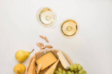 Top view of different types of cheese on wooden board, wine glasses, almond and fruits on white