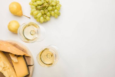 Top view of different types of cheese on wooden board, wine glasses and fruits on white