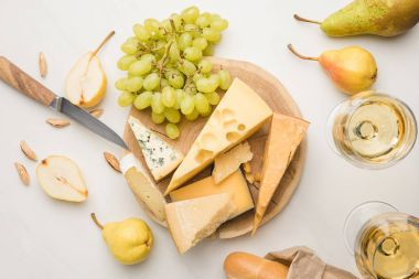 Top view of different types of cheese on wooden board surrounded by knife, fruits, almond, baguette and wine glasses on white stock vector