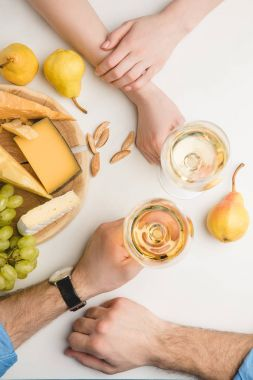 Top view of couple with wine glasses, different types of cheese, pears, grapes and almond on white