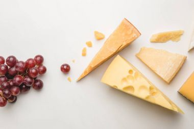 Top view of different types of cheese and grapes on white
