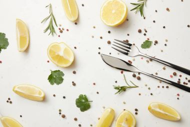 Herbs and pepper with fork and knife isolated on white