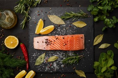 Raw salmon with herbs and lemons on slate background