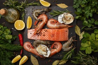 Raw salmon and assorted seafood with herbs and lemons on dark background
