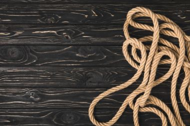 top view of brown nautical rope on dark wooden surface
