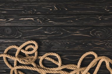 top view of brown marine rope on dark wooden planks