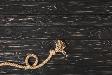 top view of knotted brown nautical rope on dark wooden surface