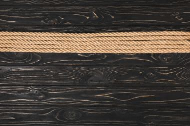 top view of brown nautical ropes placed in row on wooden background