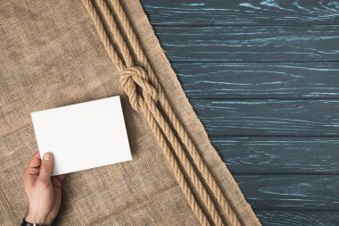 cropped image of man holding blank paper on sackcloth with knotted rope on wooden surface