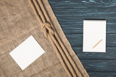 top view of empty paper on sackcloth with knotted rope and blank textbook with pencil