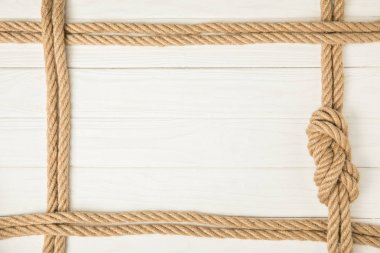 Top view of frame made by brown nautical ropes with knot on white wooden background stock vector