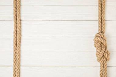 top view of frame made by brown nautical ropes with knot on white wooden background