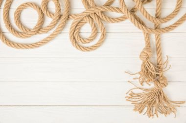 top view of brown nautical knotted rope on white wooden background